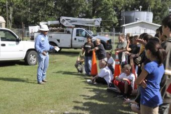 lineman outside presenting to group of young children