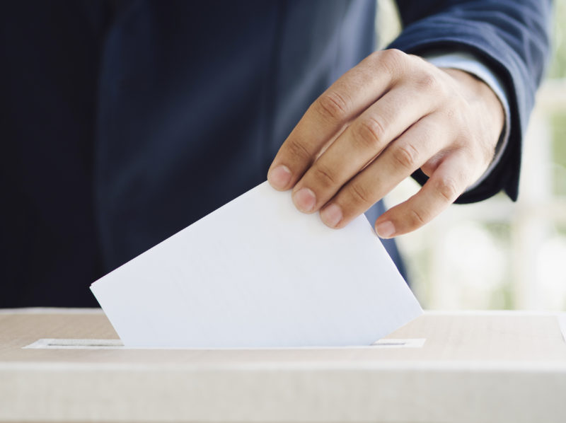 hand putting an empty ballot in election box