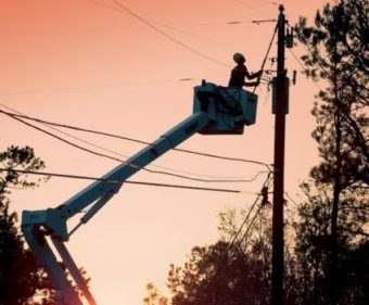 lineman in bucket truck by power pole at sunset