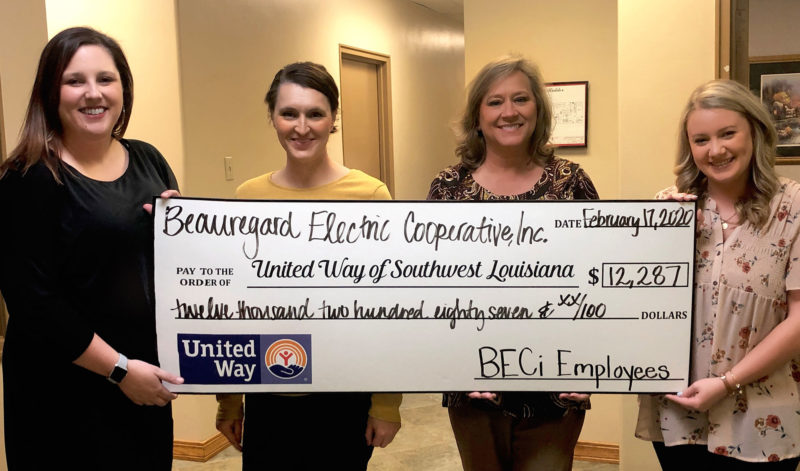 Women holding large check from BECi to United Way