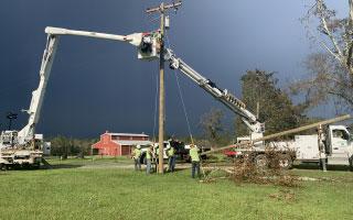linemen in bucket trucks repairing power poles during storm