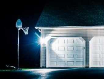 security light on garage with basketball hoop in driveway